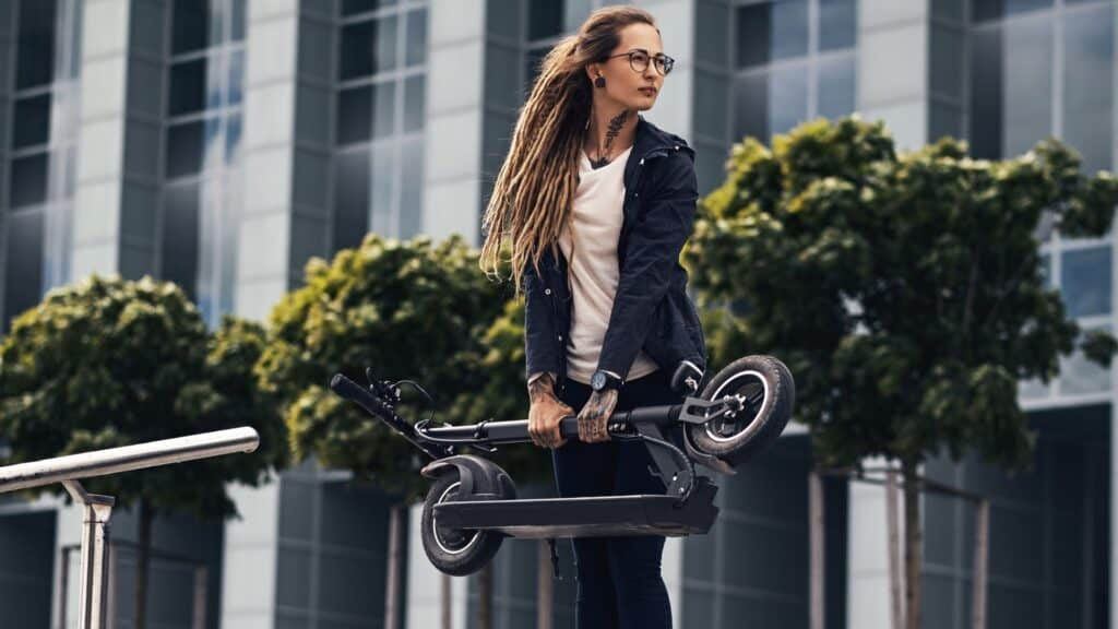 girl carrying a folding scooter